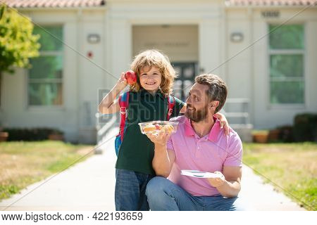 Schoolboy And Parent In Shirt Holding Lunch Box. Parent And Pupil Of Primary School Schoolboy With B