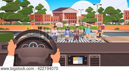 Driver Holding The Steering Wheel And Waiting Schoolchildren Crossing Road On Crosswalk Near School