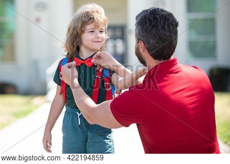 Funny Nerd. Parent Helping Kids Put Backpack On Preparing Go To School, Loving Family Dad Dressing G