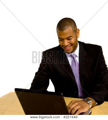 Man Working On Laptop At Desk