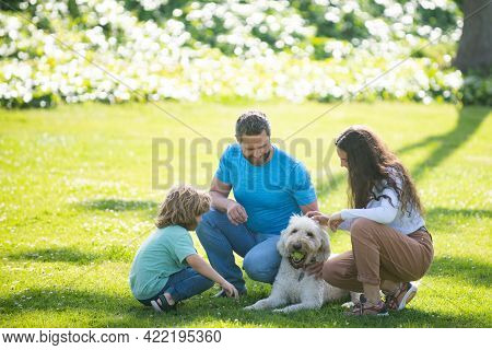 Family Relaxing In Garden With Pet Dog. The Concept Of A Happy Family. Parents And Children On Vacat