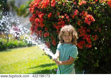 Aadorable Kid Boy Watering The Plants, From Hose Spray With Water Hose In The Garden At The Backyard