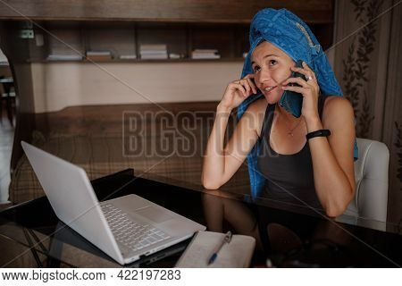 Shot Of Pretty Young Woman Using Her Mobile Phone While Working With Laptop Sitting At Home.