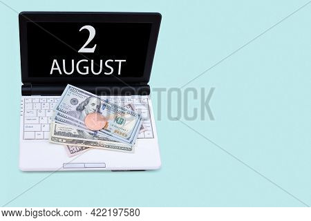 2nd Day Of August. Laptop With The Date Of 2 August And Cryptocurrency Bitcoin, Dollars On A Blue Ba