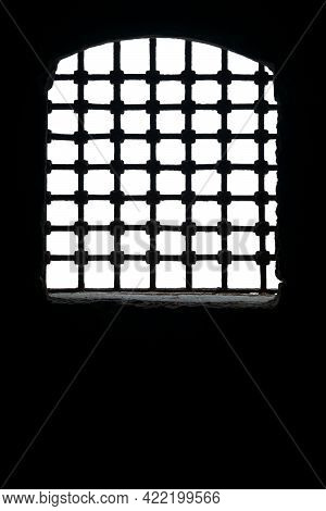 Cut Out Of Arched Window With Metal Grid In Dark Room Of Aged Building Against Daylight, Including C