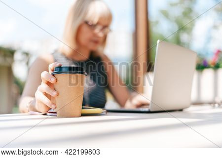 Close Up Coffe Cup. Adult Woman Typing At Laptop And Mobile Cell Phone Outside In Park. Thinking Sen
