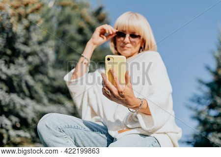 Mature Adult Woman Having A Video Call Chat With Cellphone. Happy And Smiling Girl Relax Outside In