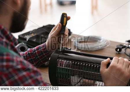 Professional Technician Repairing Electric Halogen Heater With Screwdriver At Table Indoors, Closeup