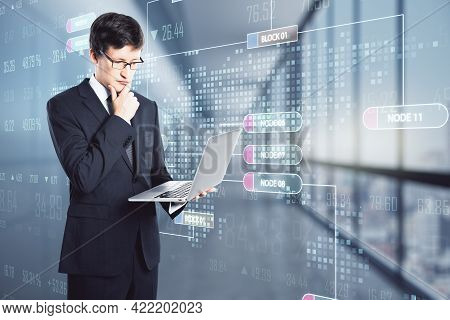 Attractive Young Businessman With Laptop And Glowing Node Interface On Blurry Office Interior Backgr