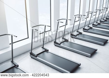 Side View Of New Grey Treadmills In Modern Gym Interior With Windows, Daylight And Concrete Floor. F
