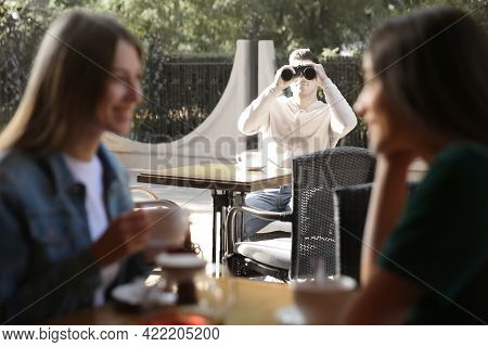 Man Spying On His Girlfriend In Outdoor Cafe. Cheating Concept