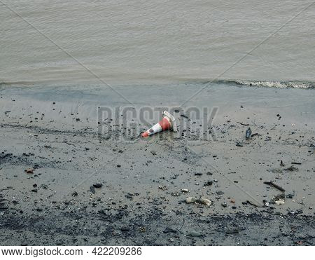 Discarded Orange And White Traffic Cone On Beach Or Drying River Bed