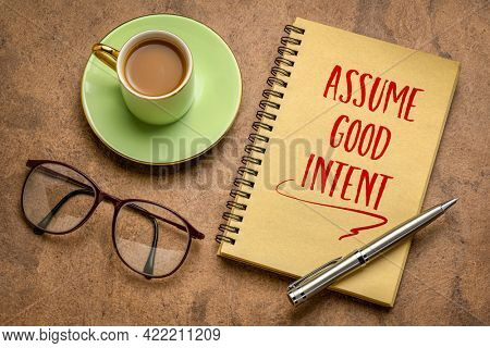 assume good intent inspirational handwriting in a spiral notebook with a cup coffee, positivity and personal development concept