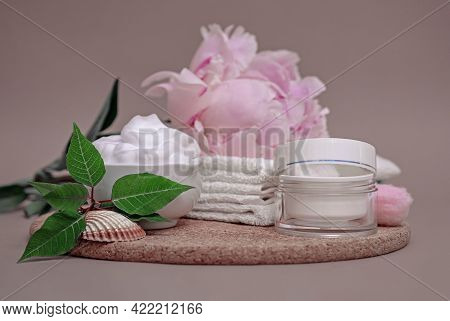 On A Wooden Stand White Skin Care Cream, White Clean Towels, Pink Peony, White Jar And Sponge, Skin
