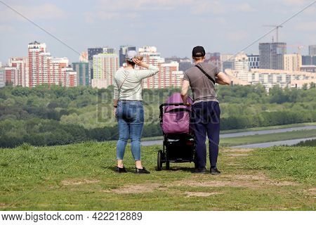 Couple With Baby Pram Standing On Top Of A Hill On Background Of Summer City And Buildings Under Con