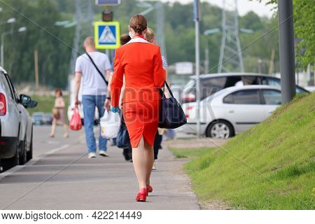 Woman In A Red Business Suit Walks Down The City Street On Background Of People. Flight Attendant Af