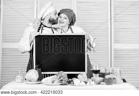 Share Joy. Man And Woman Chef Cooking Food Together. Couple With Blackboard For Advertisement. Lovel