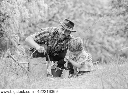 Boy And Father In Nature With Watering Can. Gardening Tools. Planting Flowers. Dad Teaching Little S
