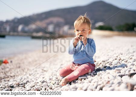 Pensive Kid Sits And Gnaws A Pebble, Holding It With Both Hands On A Pebble Beach By The Sea Against