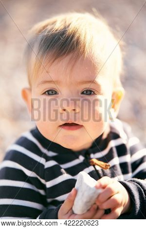 Little Boy In A Striped Overalls Sits On A Pebble Beach And Holds A Pebble In Front Of Him. Close-up