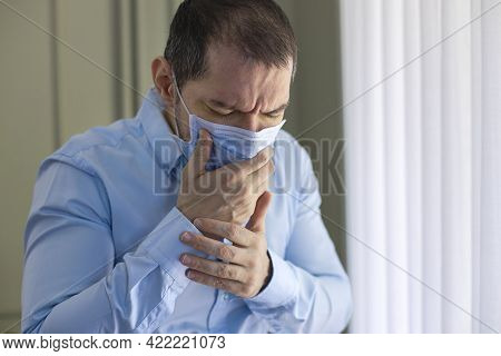 Young Man Coughing In A Medical Mask