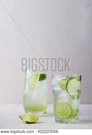 Summer Cool Drink With Ice Cubes And Lime In A Transparent Glass On A Light Pastel Background. Summe