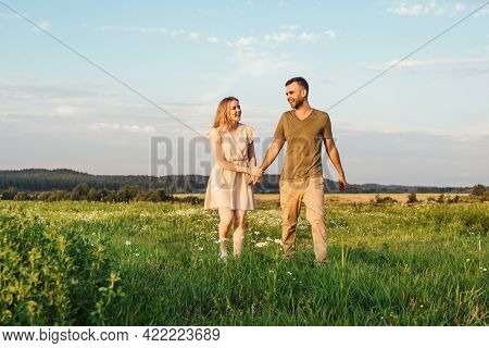 Young Happy Family With Little Boy Run In Field And Flying A Kite. Front View.