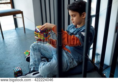 Child trying to solve difficult puzzle cube