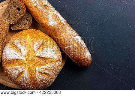 Heap Of Bread On A Black Background. Crispy Bread Top View. Round Bread, Baguette, Loaf Of Rye Bread