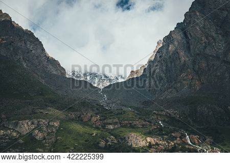 Atmospheric Landscape With Mountain Stream In Narrow Valley Among High Rocky Mountains. Low Clouds O