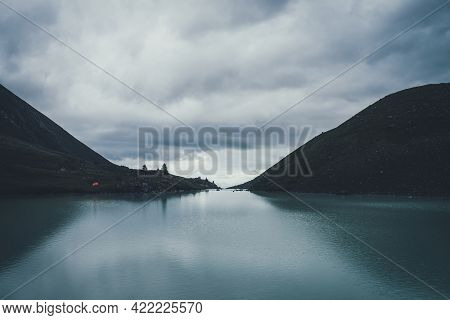 Dark Atmospheric Landscape With Orange Tent Near Mountain Lake In Highland Valley Under Cloudy Sky I