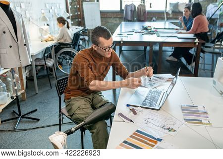 Young disable man sitting by table and working over fashion collection in large workshop