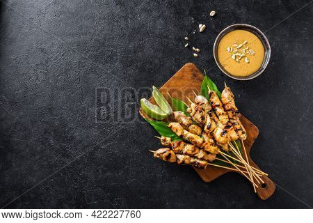 Chicken Grilled Satay Skewers Served With Lime And Peanut Sauce On Black, Copy Space. Asian Thai Sty