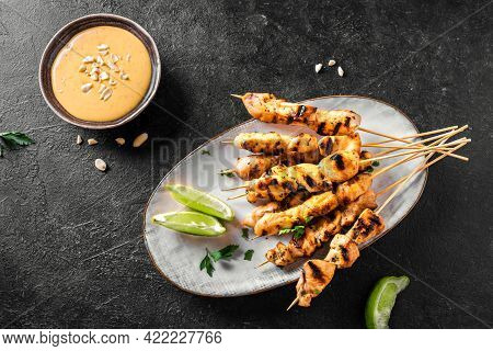 Chicken Grilled Satay Skewers Served With Lime And Peanut Sauce On Black, Top View. Asian Thai Style