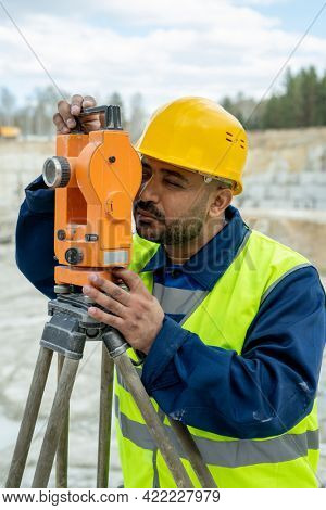 Land surveyor in workwear and hardhat working with geodetic station