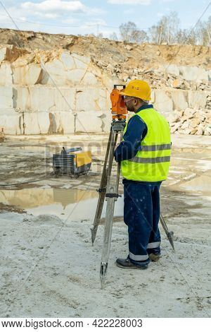 Young surveyor in workwear using geodetic station on construction place