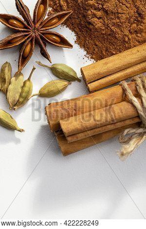 A Slide Of Ground Cinnamon, Cinnamon Rolls, Cardamom, Anise On A White Background, Studio Shot, Copy