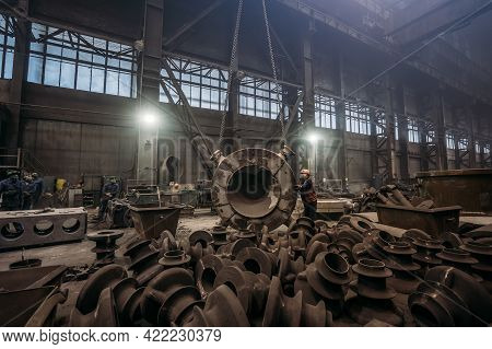 Large Cast Iron Product Moved On Girder Crane In Workshop Of Metallurgical Plant. Foundry, Heavy Ind