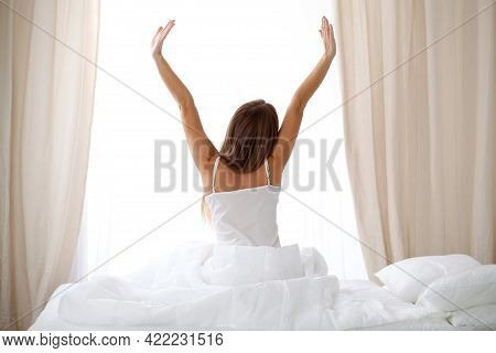 Woman Stretching In Bed After Wake Up, Back View, Entering A Day Happy And Relaxed After Good Night