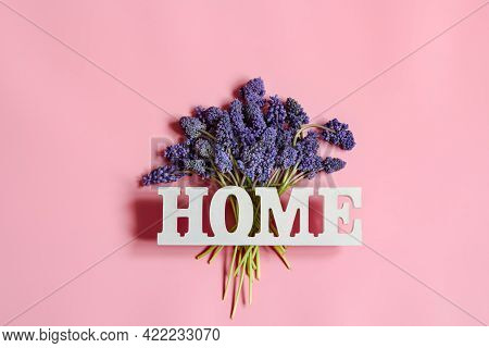 Minimalistic Spring Composition With Blue Flowers And The Decorative Word Home.