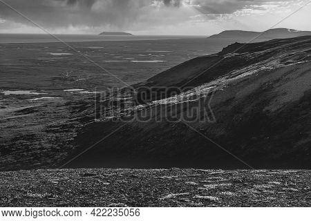 A Black And White Landscape With Sledge Island Off Nome Alaska In The Distance.