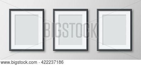 Realistic Set Of Three Vertical Blank Picture Frame Isolated On Grey Wall Background. Empty Photo Fr