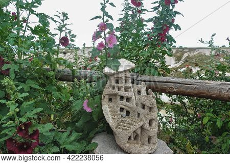 Mallow Blossoms By The Wooden Hedge. Long Stems, Red And Pink Flowers. Among The Green Leaves Is A F