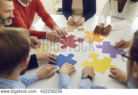 Diverse Multiethnic People Group Collaborating Assembling Puzzle Pieces Together