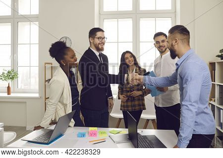 Male Leader Of A Multiracial Business Team Greets A New Team Member Shaking His Hand.