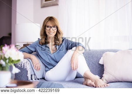 Happy Middle Aged Woman Relaxing On The Couch At Home
