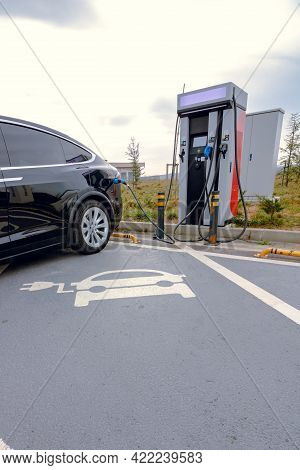Ev Car Plugged In Charger And Ev Charger Station. Electric Car Charger Station Near The Highway. Ele