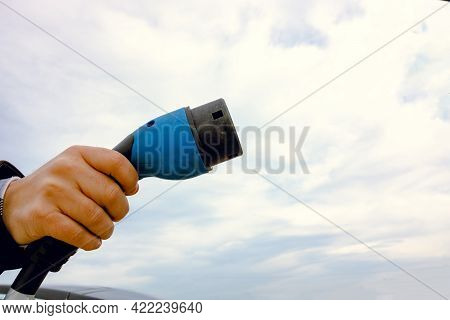 Man Holding A Ev Charger Against The Cloudy Sky. Copy Space. Ev Charger. Electric Vehicle Charging.