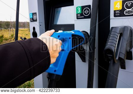 Man Taking A Fast Ev Charger From Ev Charging Station In Focus. Fast Ev Charger Station. Electric Ve