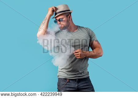 Bearded Male In Hat And Sunglasses Smoking A Vapor Cigarette As An Alternative To Tobacco. Studio Sh
